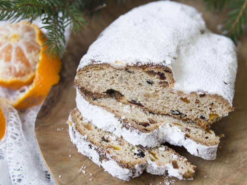 传统欧洲圣诞节酥皮点心,芬芳家庭焙制stollen,用香料和干果 切在木桌上 免版税库存照片