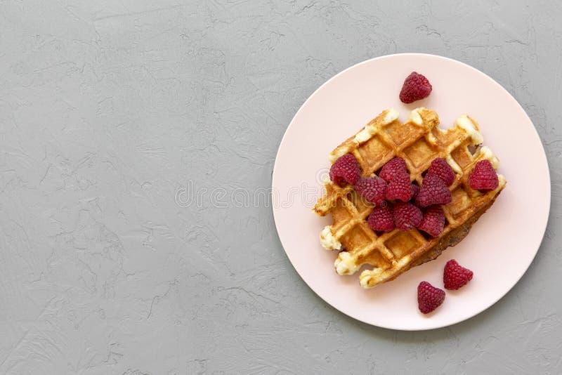 传统比利时华夫饼干用在桃红色板材的莓在凝结面,顶视图 免版税库存图片