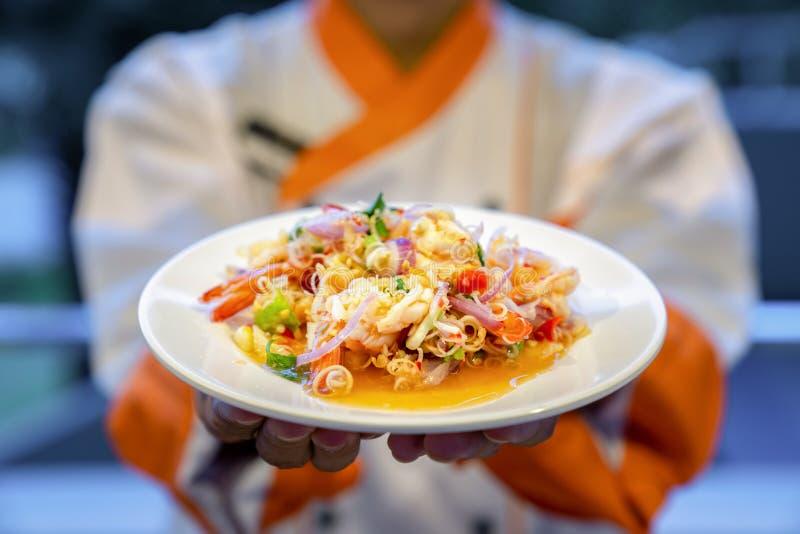 传统泰国辣面条细面条用海鲜虾乌贼和泰国草本在厨师手上 免版税图库摄影