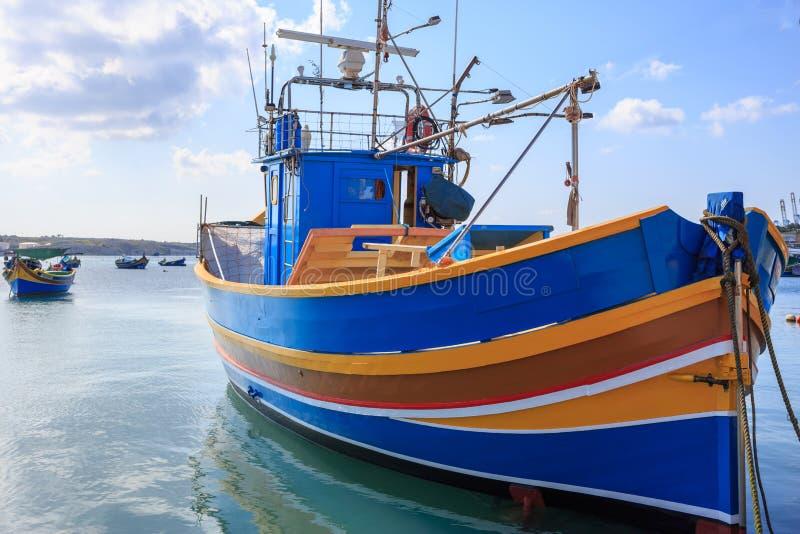 传统渔船, luzzu,停住在Marsaxlokk,马耳他 与云彩和村庄背景的蓝天 关闭视图 免版税图库摄影