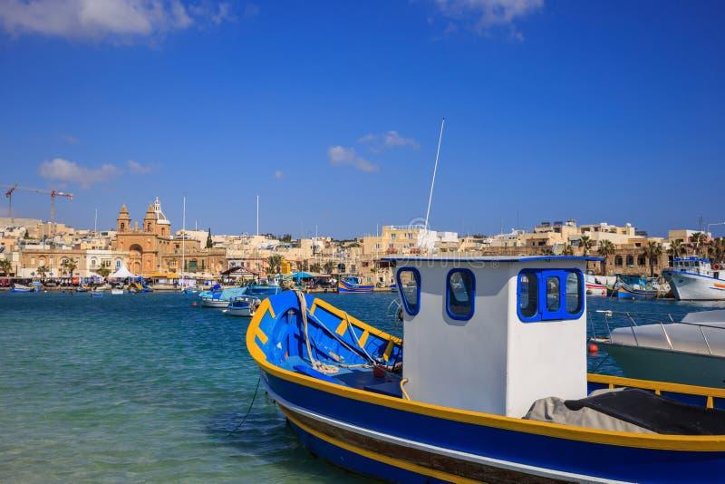 传统渔船, luzzu,停住在Marsaxlokk,马耳他 蓝天和村庄背景 关闭视图 免版税库存照片