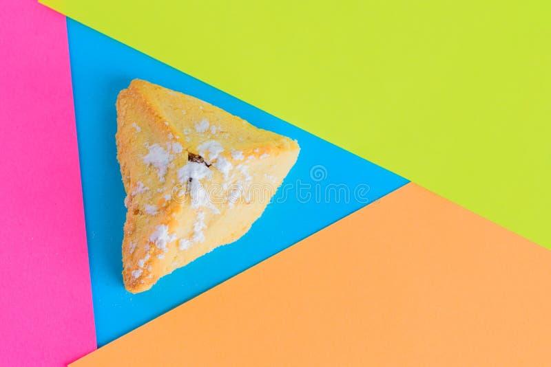 传统犹太酥皮点心,Hamantaschen,服务在现代五颜六色的背景的普珥节期间 顶上的视图 免版税库存照片