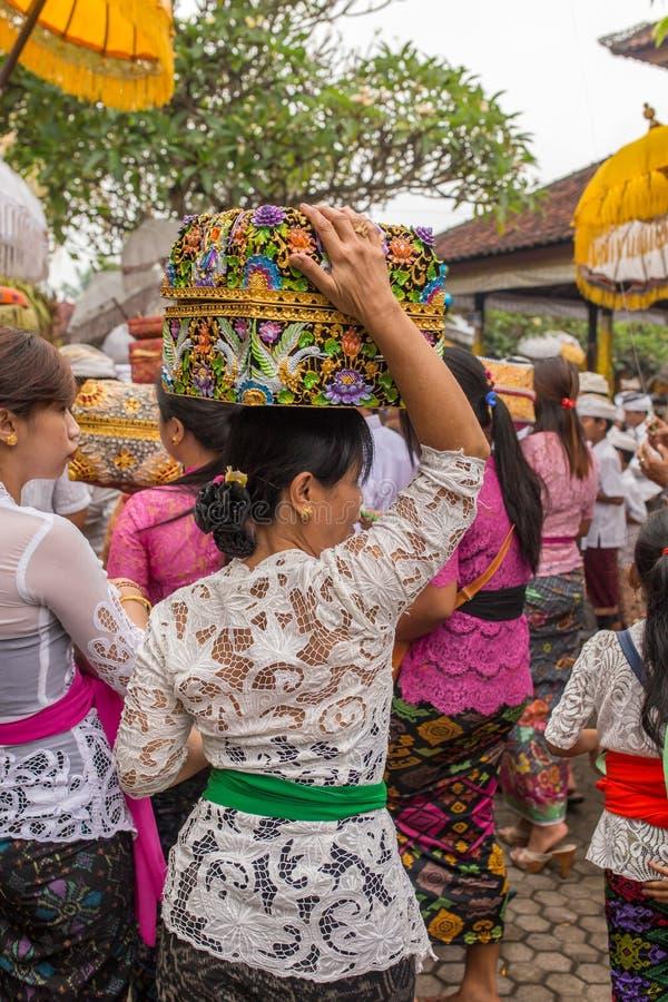 传统礼服布裙的未认出的巴厘语妇女有宗教提供的在Galungan庆祝时在巴厘岛 库存图片