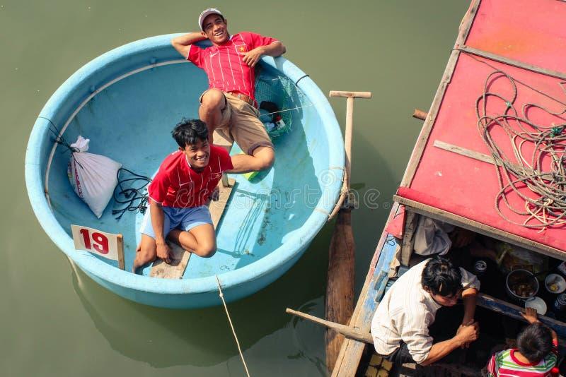 传统篮子小船的两愉快的微笑的年轻人在河 免版税库存照片