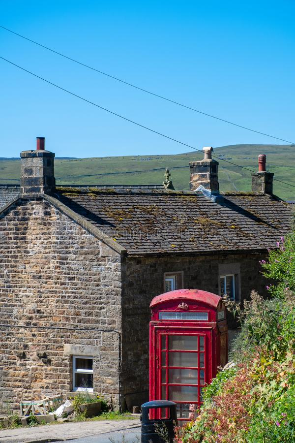 传统红色电话箱子和村庄 免版税库存图片