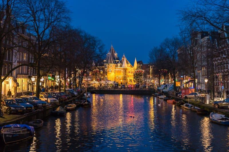 传统老大厦和小船在晚上在阿姆斯特丹 免版税库存图片
