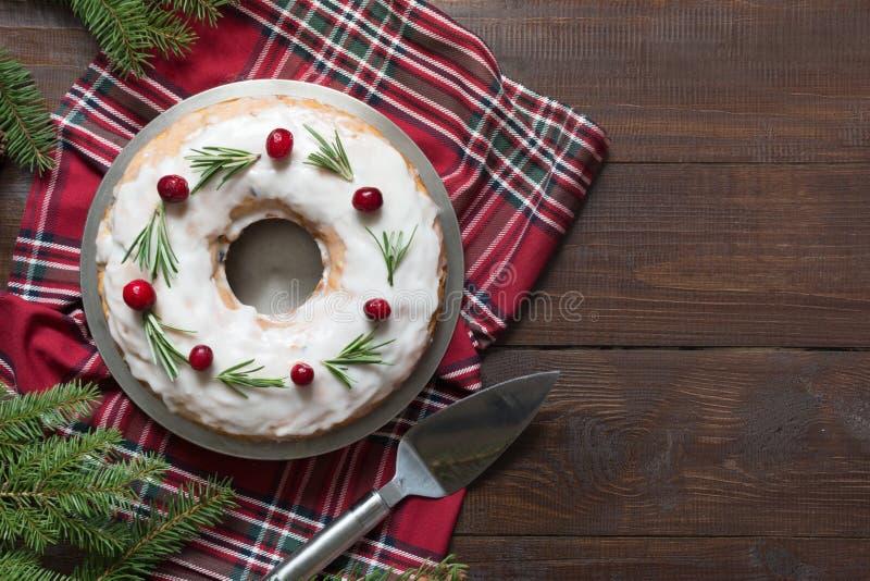 传统自创圣诞节蛋糕用装饰品蔓越桔和迷迭香在板材 与空间的顶视图文本的 库存图片