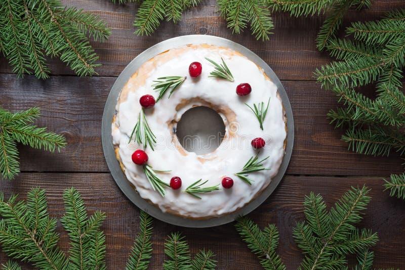 传统自创圣诞节蛋糕用装饰品蔓越桔和迷迭香在装饰板材 与空间的顶视图文本的 免版税库存图片