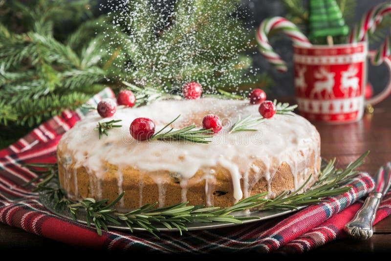 传统自创圣诞节蛋糕用装饰品蔓越桔和迷迭香在装饰板材 搽粉用糖粉 图库摄影