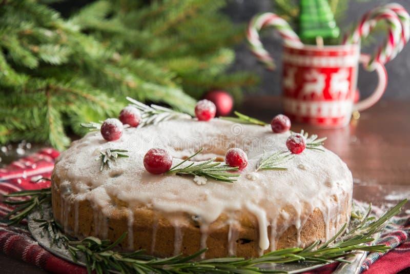 传统自创圣诞节蛋糕用装饰品蔓越桔和迷迭香在装饰板材 免版税库存图片