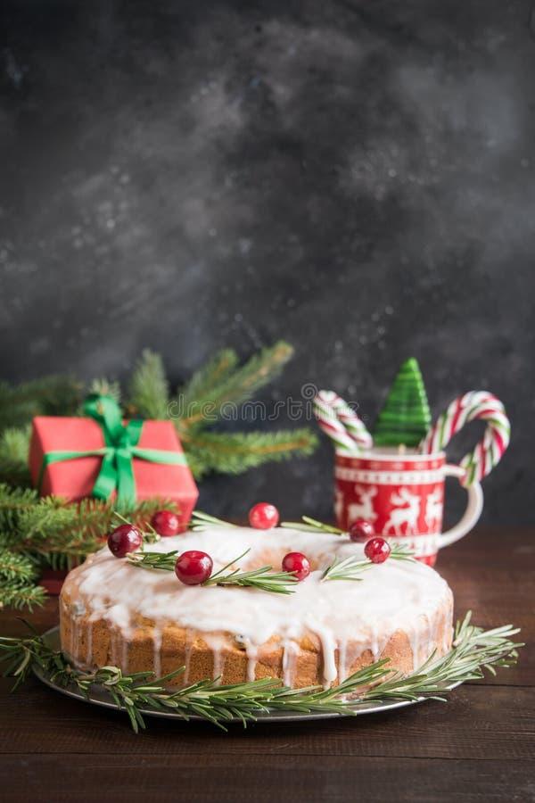 传统自创圣诞节蛋糕用装饰品蔓越桔和迷迭香在装饰板材 图库摄影