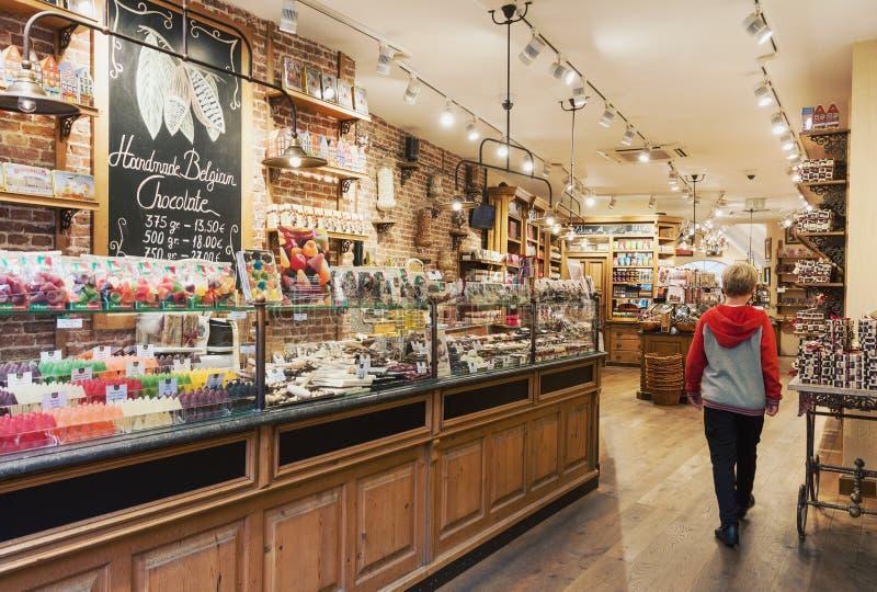 传统舒适比利时巧克力商店内部与糖果和甜点variey  免版税库存照片