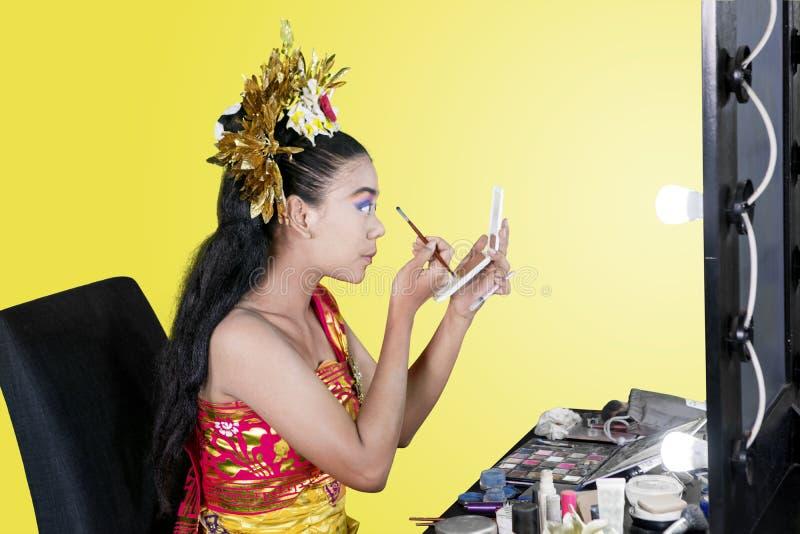 传统舞蹈家在演播室应用眼影膏 免版税库存照片