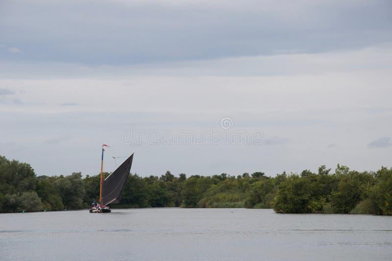 传统英国帆船:一艘诺福克小舟摆渡船,在一灰色天 库存照片