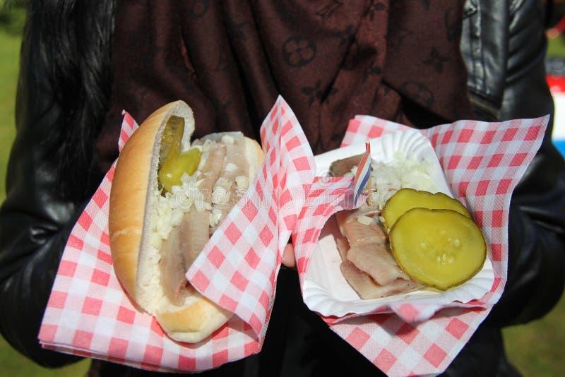 传统荷兰食物-鲱鱼钓鱼用葱和荷兰旗子在库肯霍夫上,荷兰快餐市场  ?? 免版税库存图片