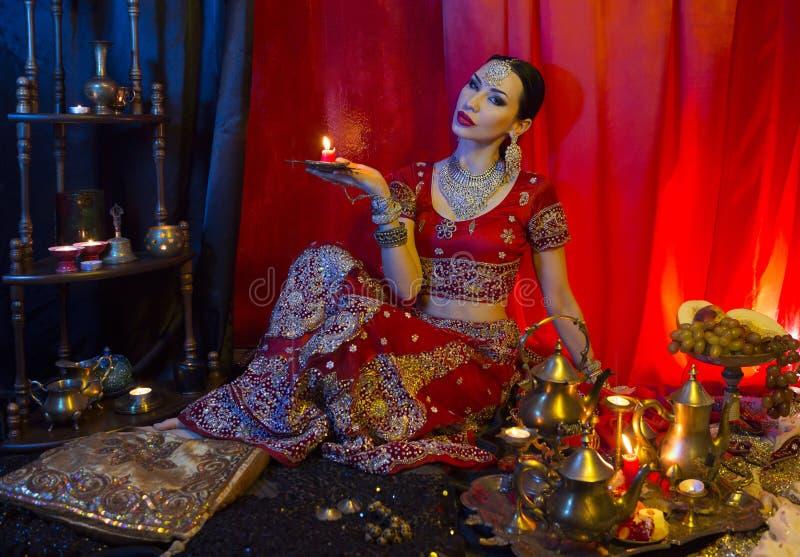 传统莎丽服衣物和东方首饰的美丽的年轻印度妇女与蜡烛 免版税库存照片