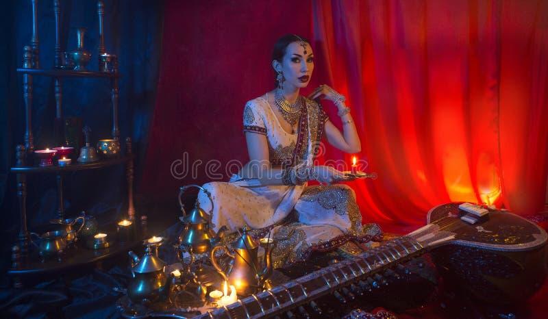 传统莎丽服衣物和东方首饰的美丽的年轻印度妇女与蜡烛 库存照片