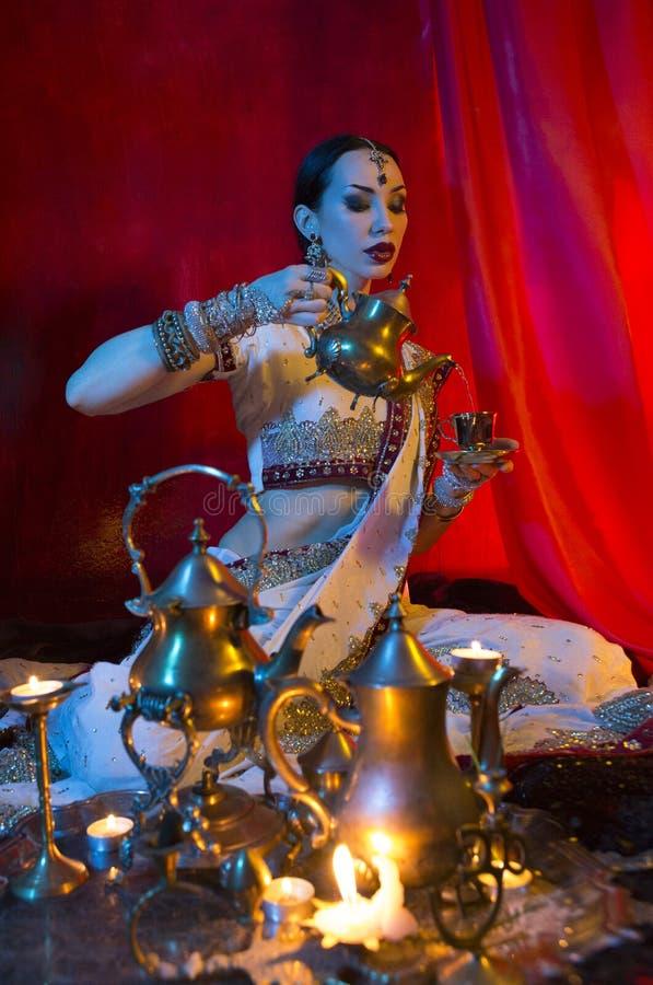 传统莎丽服衣物的美丽的年轻印度妇女用东方首饰倾吐的茶到杯里 库存照片