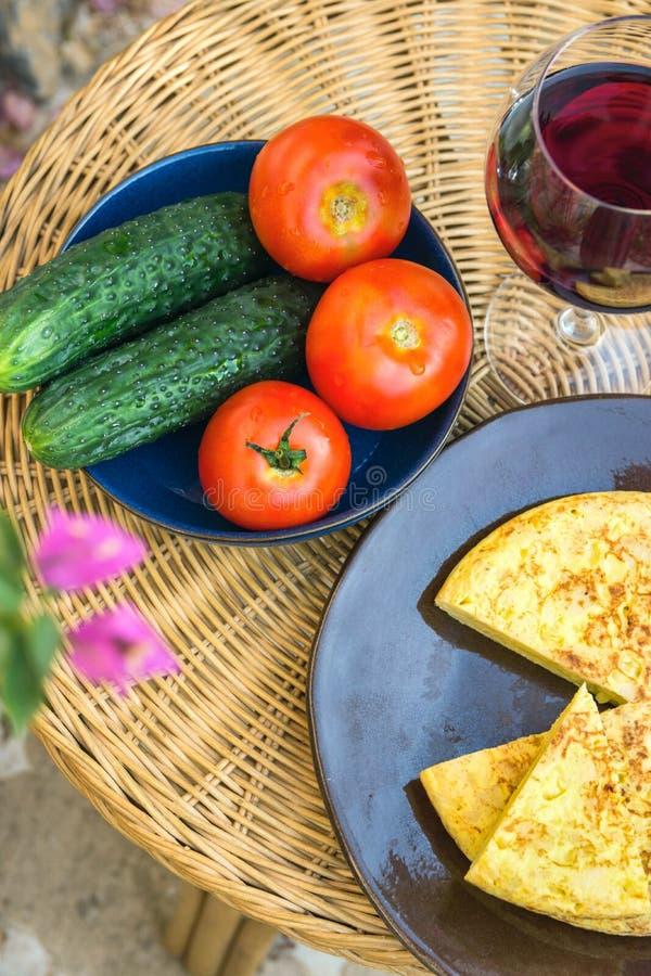 传统西班牙煎蛋玉米粉薄烙饼用被删去的土豆鸡蛋楔住有机菜蕃茄黄瓜杯红葡萄酒表 库存图片