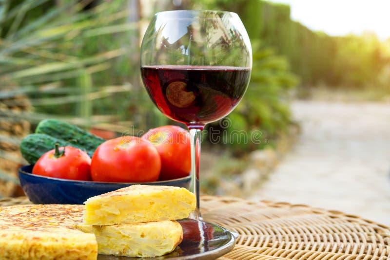 传统西班牙煎蛋玉米粉薄烙饼用被删去的土豆鸡蛋楔住有机菜蕃茄黄瓜杯红葡萄酒 库存图片