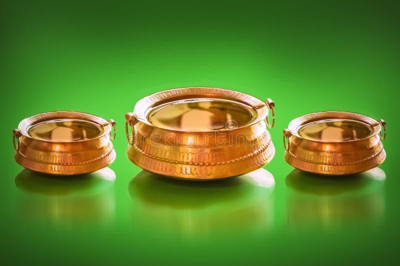 传统黄铜罐以有很多幸运的魅力的水和硬币里面 库存图片