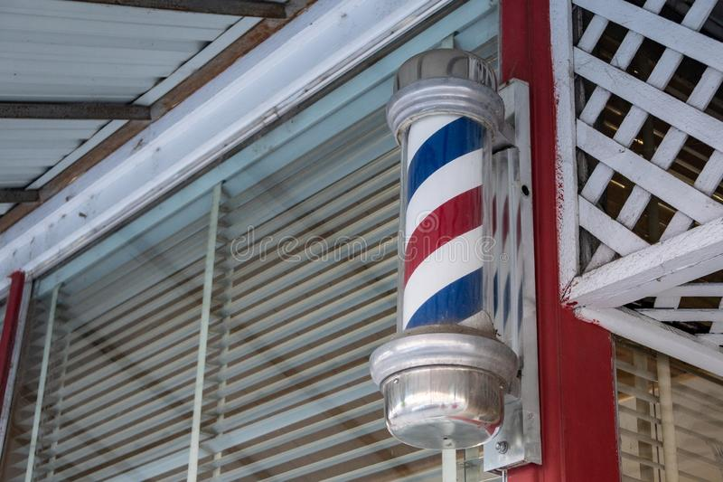 传统,古板的镶边理发店杆在沙龙外面 免版税库存照片