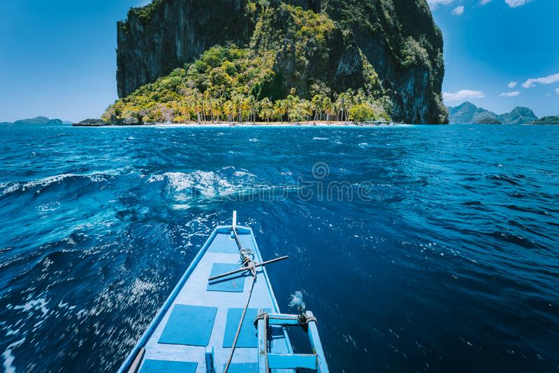 传统banca小船方法在圆Pinagbuyatan海岛前面的一个小伊比尔海滩有巨大的石灰石峭壁的 免版税库存照片