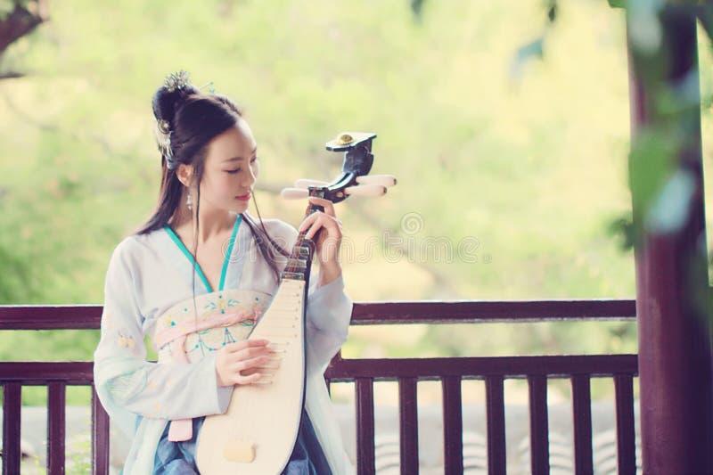 传统Hanfu礼服的中国妇女,弹奏负子蟾的传统仪器 免版税库存图片