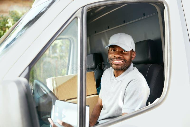 传讯者交付 驾驶送货车的黑人司机 库存图片