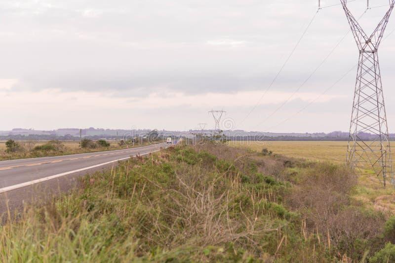 传输塔和机动车路 库存照片