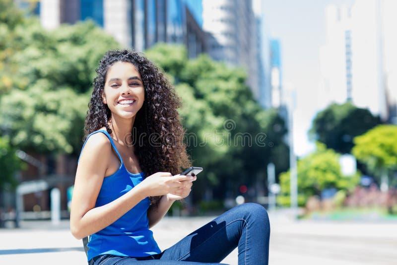 传送与电话的笑的年轻妇女信息在城市 免版税图库摄影