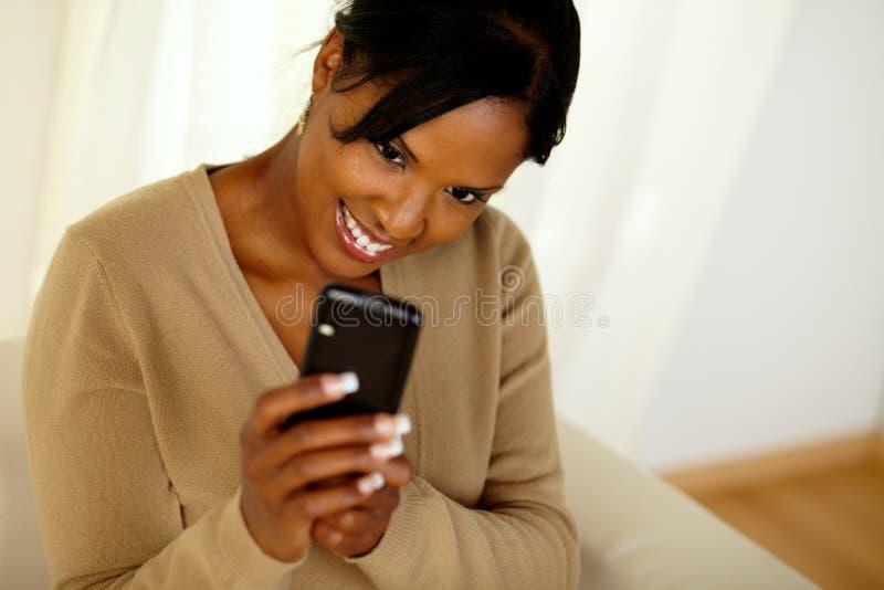 传送信息的愉快的黑人女性由移动电话 库存图片
