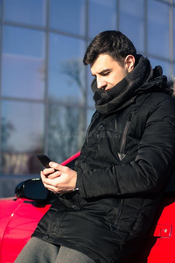 传送信息的年轻人在现代跑车附近 图库摄影