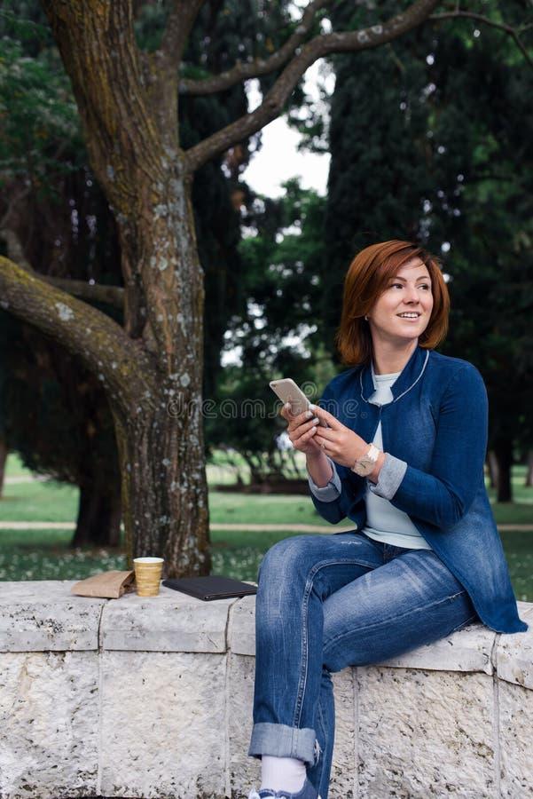 传送在她的电话的美丽的妇女信息在公园 库存图片