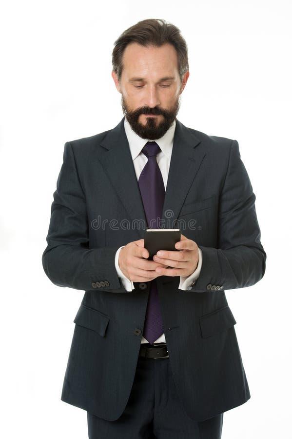传送重要信息 商人正式衣服拿着智能手机 发短信集中的人有胡子的商人 免版税库存图片