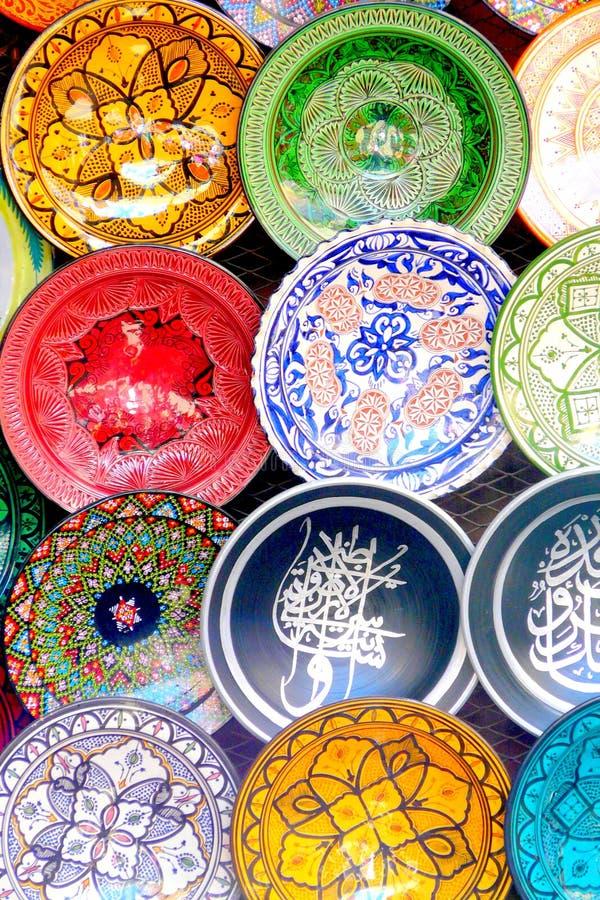 传统五颜六色的摩洛哥精巧彩色陶器瓦器盘在马拉喀什,摩洛哥麦地那的souk的一家典型的古老商店  免版税库存照片