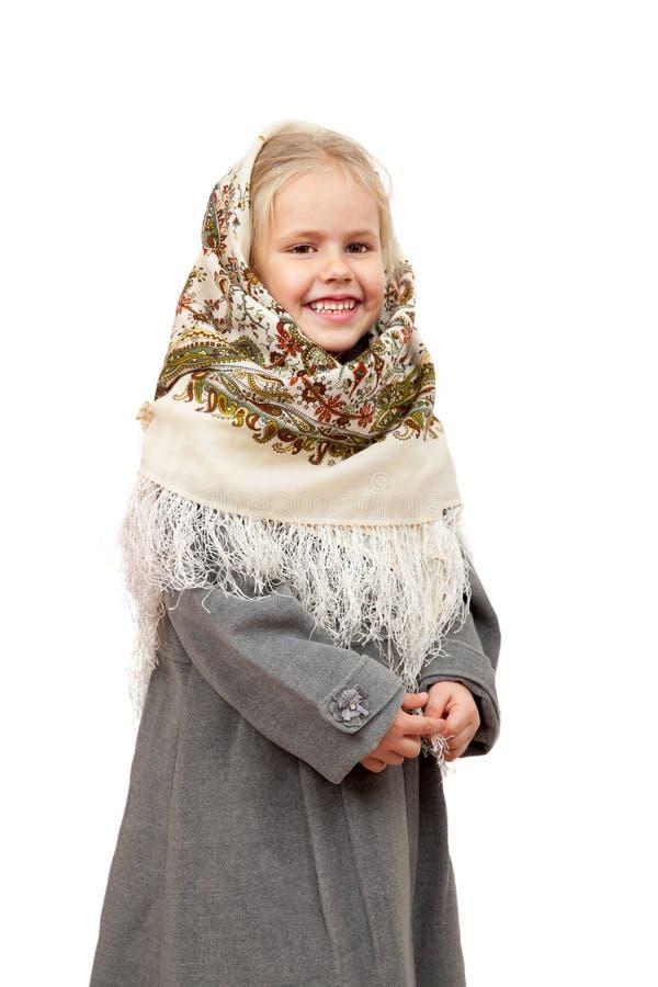 传统俄国披肩的一个微笑的小女孩 免版税库存图片