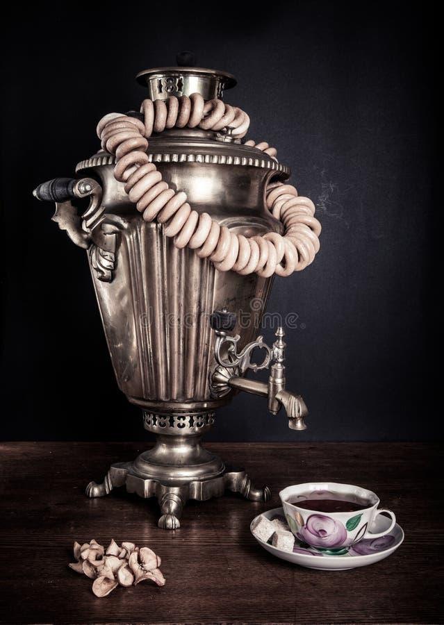 传统俄国茶 俄国式茶炊、百吉卷和干苹果 库存图片