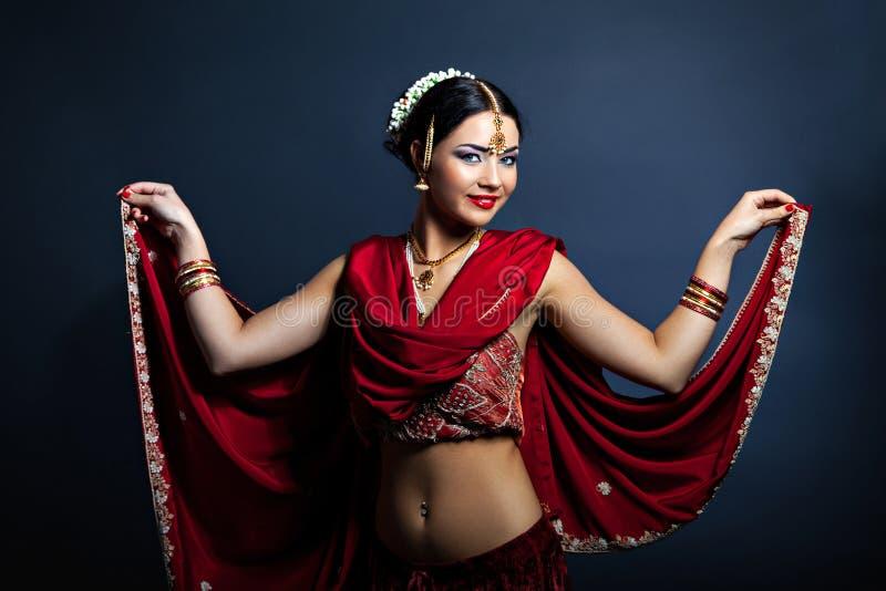 传统印地安衣物跳舞的年轻微笑的妇女 免版税库存照片