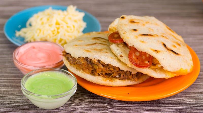 传统可口arepas、切细的鸡鲕梨和切达干酪和切细的牛肉用搓碎干酪,鲕梨 库存图片