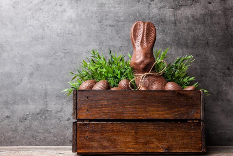 传统复活节巧克力兔宝宝和鸡蛋在一个木板箱里面 库存图片