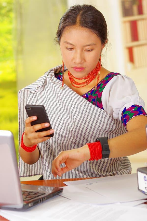 戴传统安地斯山的衣物和眼镜,坐的工作的年轻俏丽的女孩在有便携式计算机的办公桌旁边 免版税图库摄影
