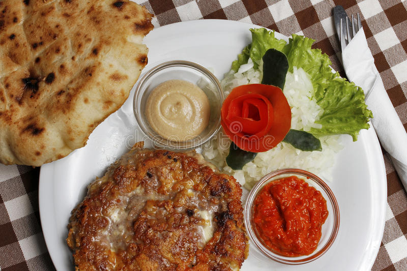 传统巴尔干pljeskavica用乳酪烤了肉用lepinja面包 免版税库存图片