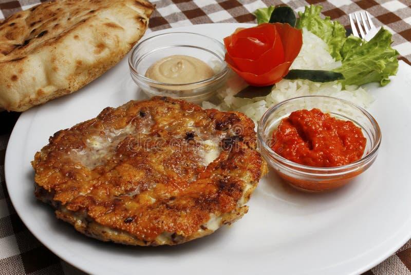 传统巴尔干pljeskavica用乳酪烤了肉用lepinja面包 图库摄影