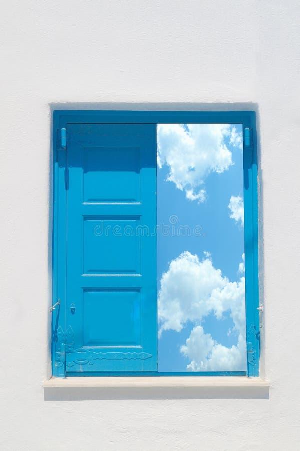 传统希腊窗口对白色墙壁和多云天空 库存图片