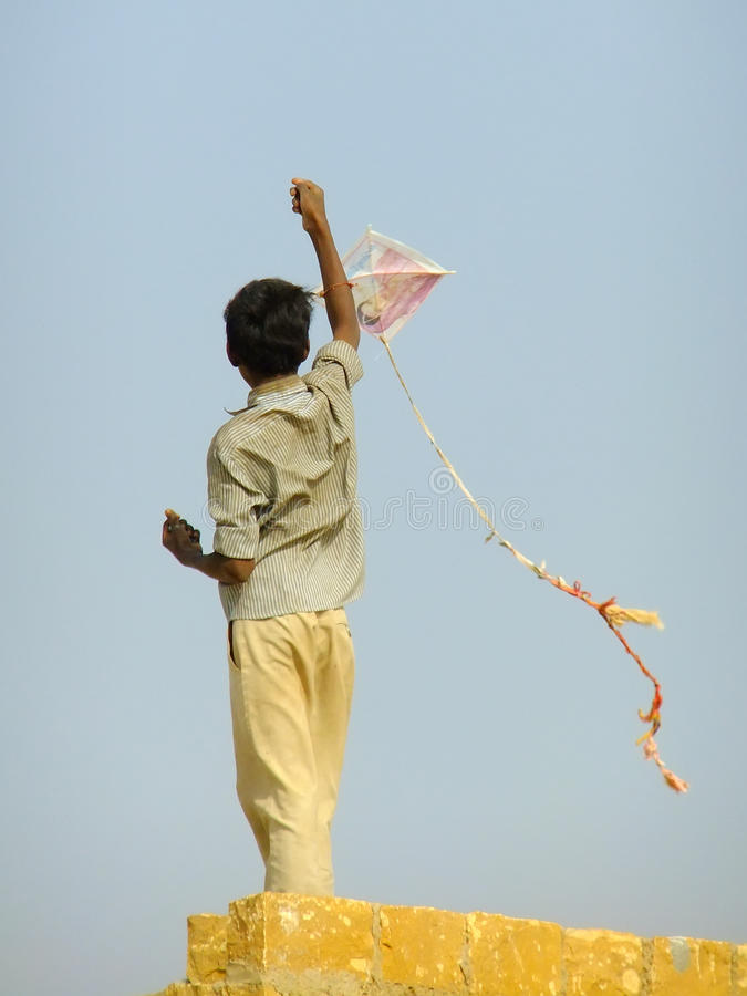 从传统房子屋顶的印地安男孩飞行风筝在Tha 免版税库存照片
