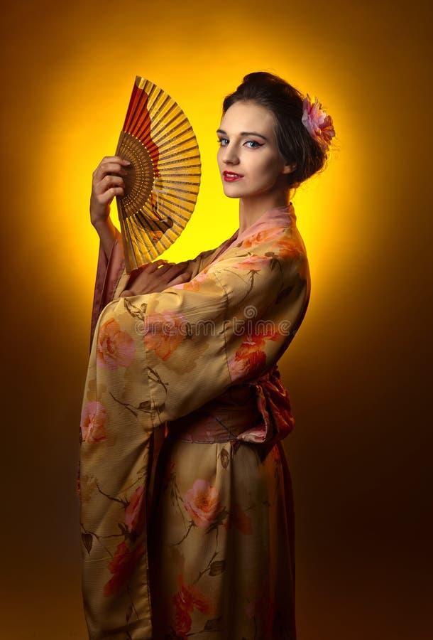 传统日本和服的年轻美丽的妇女有爱好者的 免版税库存图片