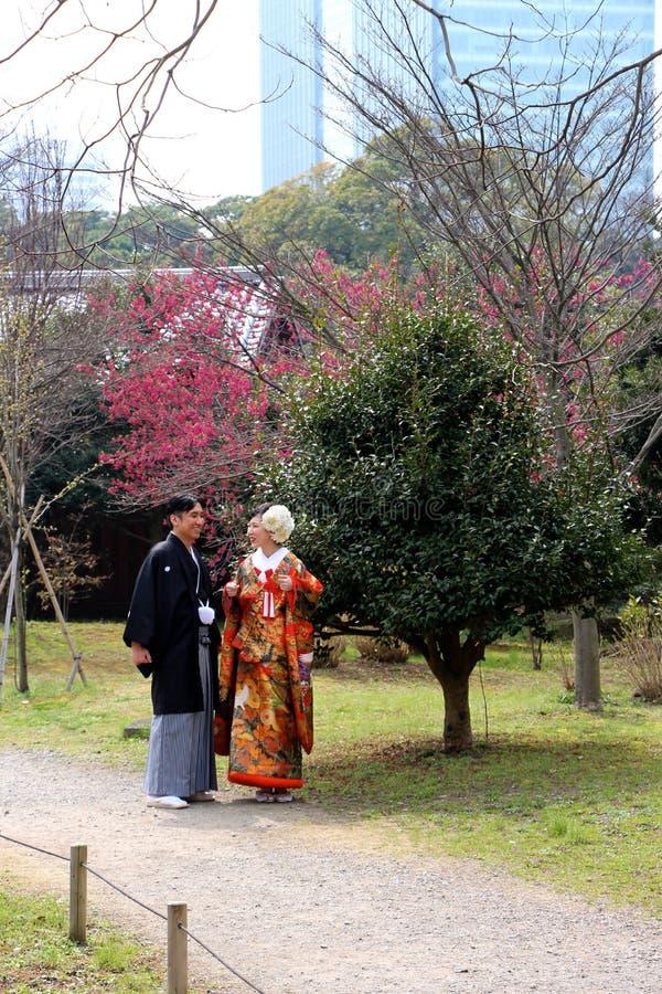 传统年轻日本夫妇为漫步在春天期间的公园 免版税库存图片