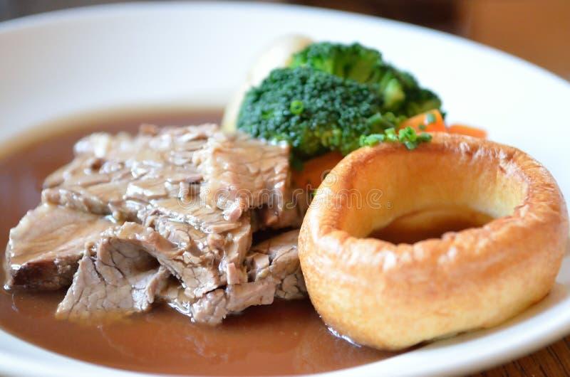 传统星期天烤牛肉晚餐用约克夏布丁和小汤 库存图片