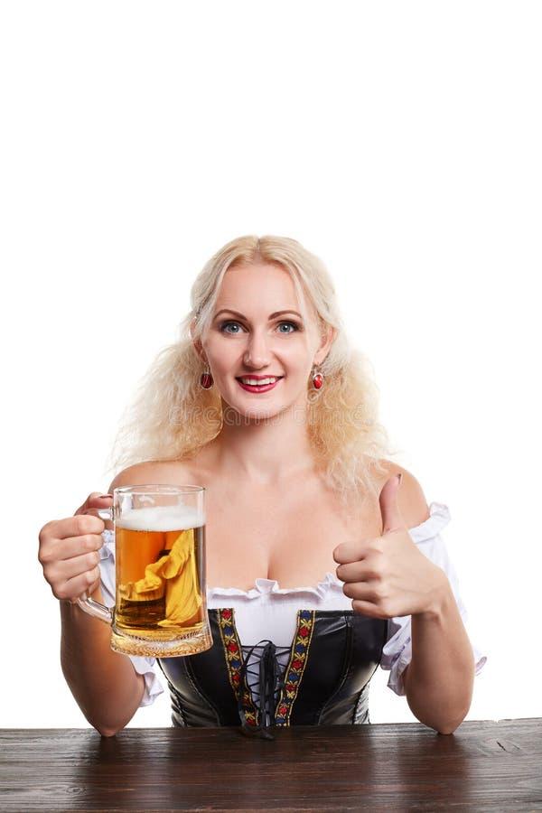 传统服装的美丽的年轻白肤金发的女孩喝在oktoberfest啤酒啤酒杯外面 免版税库存图片